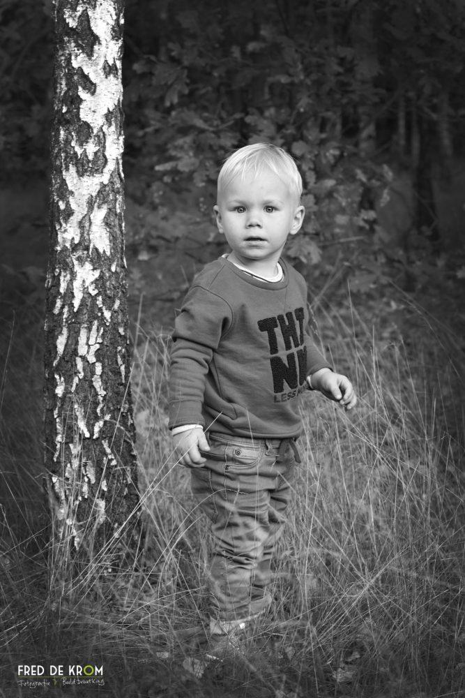 portretfoto van kind in bos_zwart wit foto