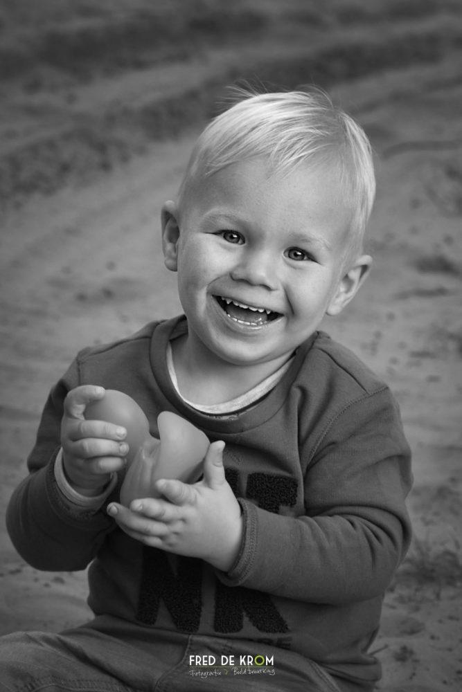 zwart wit portretfoto van kind op duin in zand