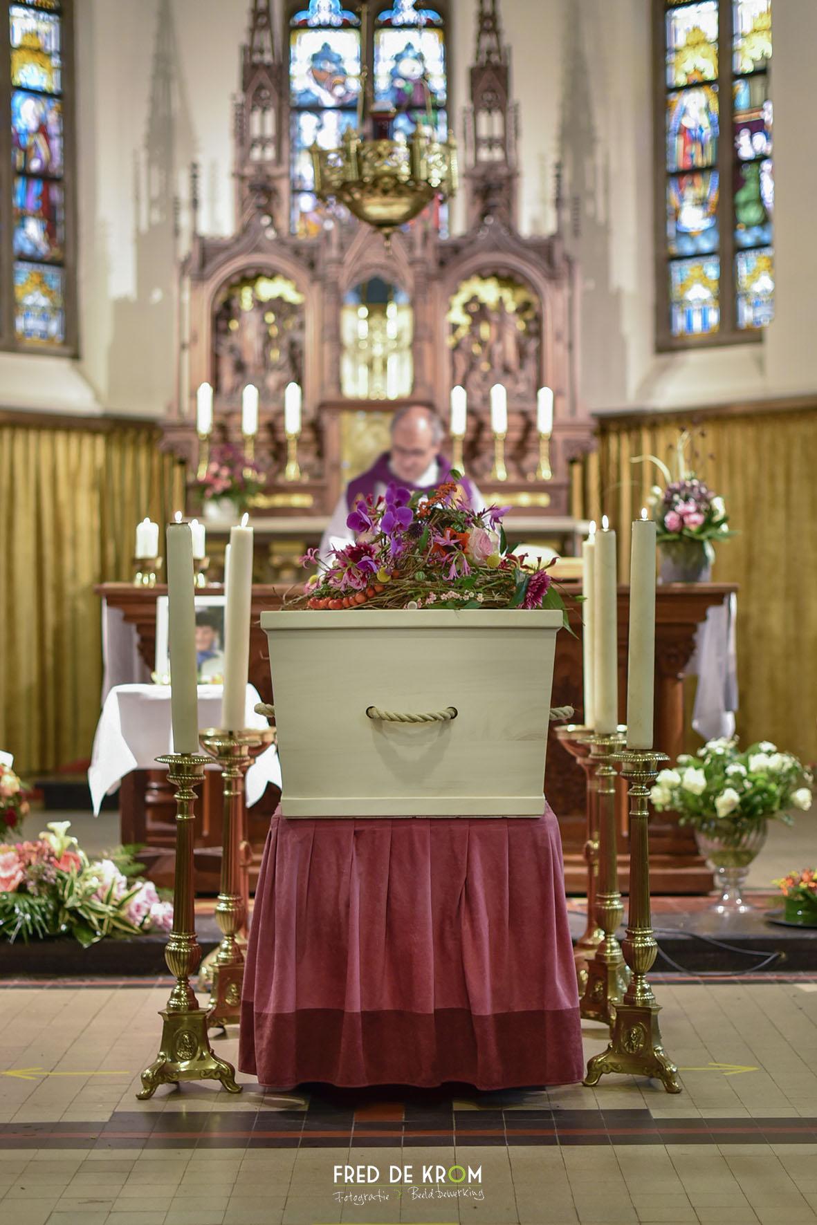 Foto tijdens begrafenis in Veldhoven, kist tussen kaarsen en voor geestelijke.