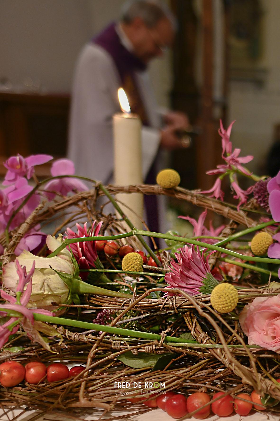 Foto tijdens begrafenis in Veldhoven, bloemen en kaars bij kist.