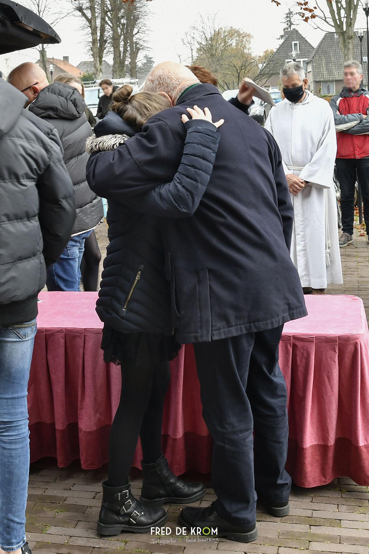 Foto tijdens begrafenis in Veldhoven, kist in rouwauto gezet. Troostende schouder.