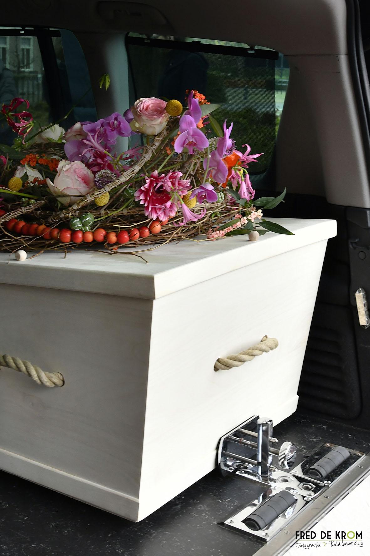 Foto tijdens begrafenis in Geldrop, kist in rouwauto gezet.