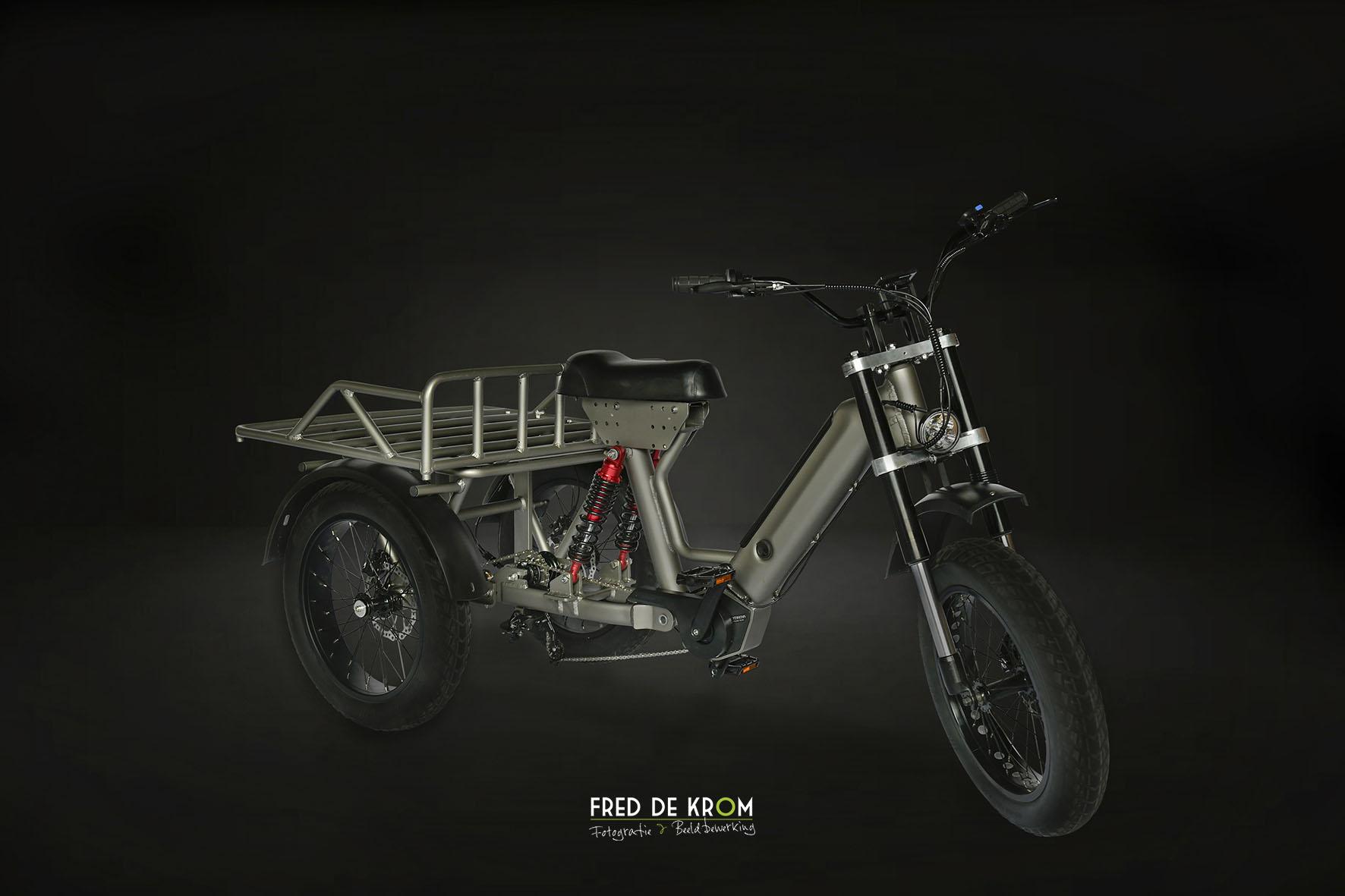 Elektrische driewieler met bagagerek en dikke banden.