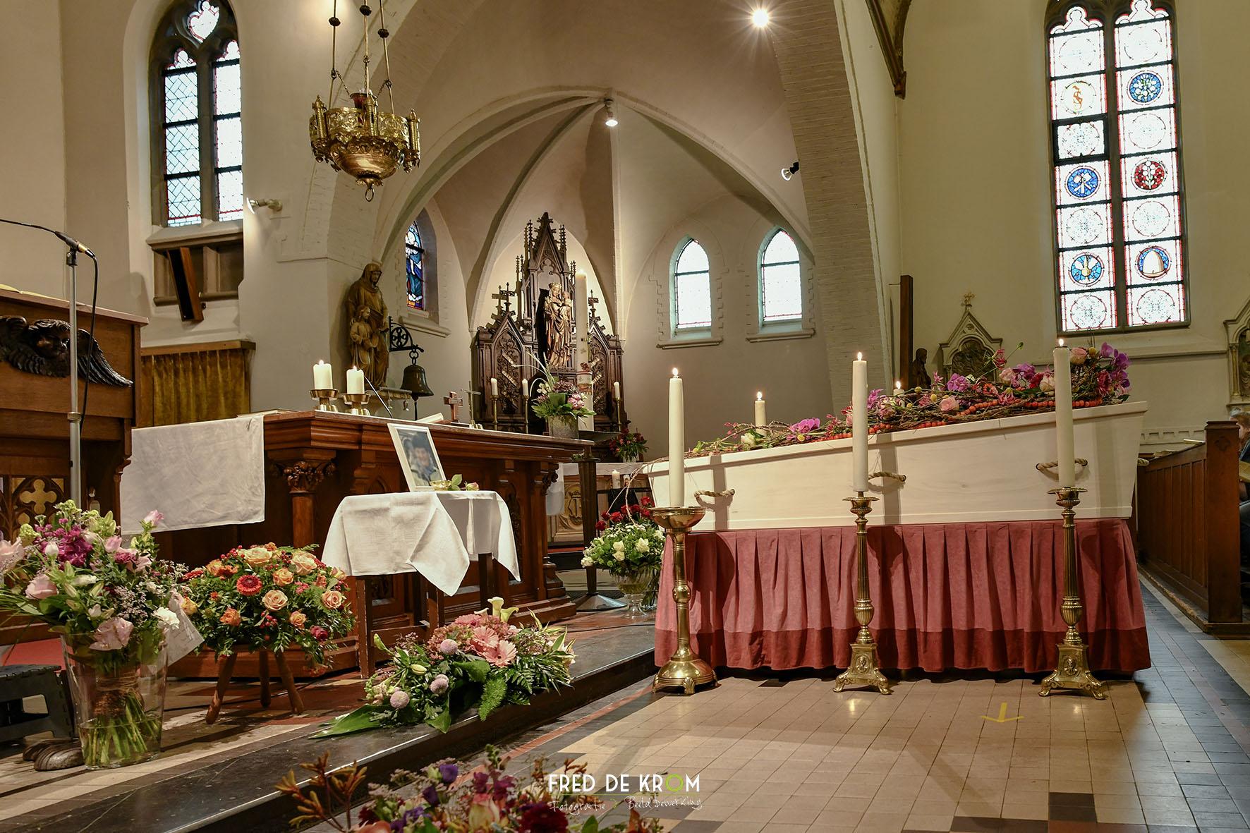 Foto tijdens begrafenis in Veldhoven, kist voor het altaar, tussen kaarsen.